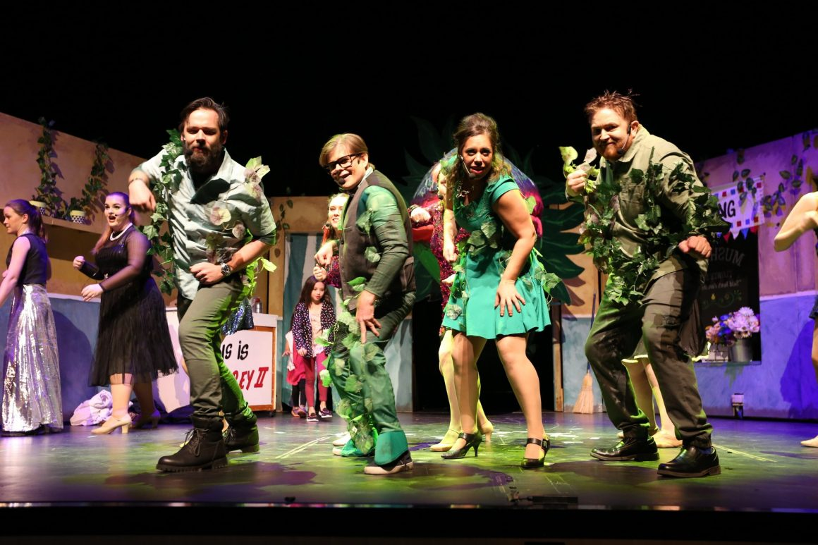 Four people on stage dressed in green