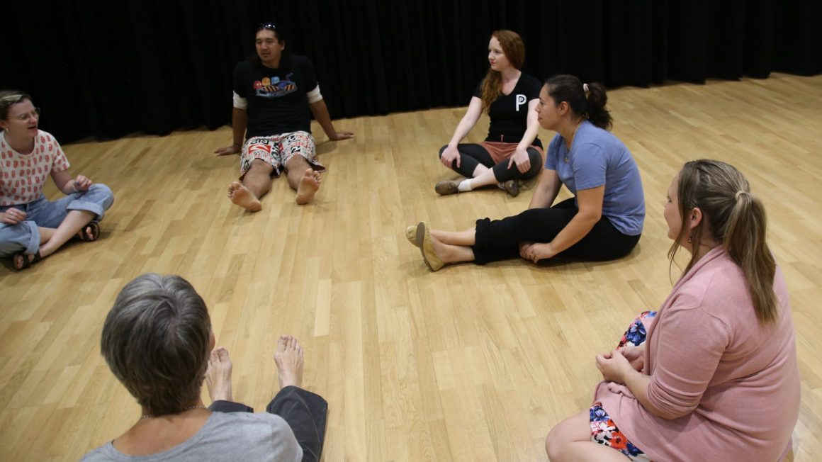 Students sitting in a circle participating in improv class